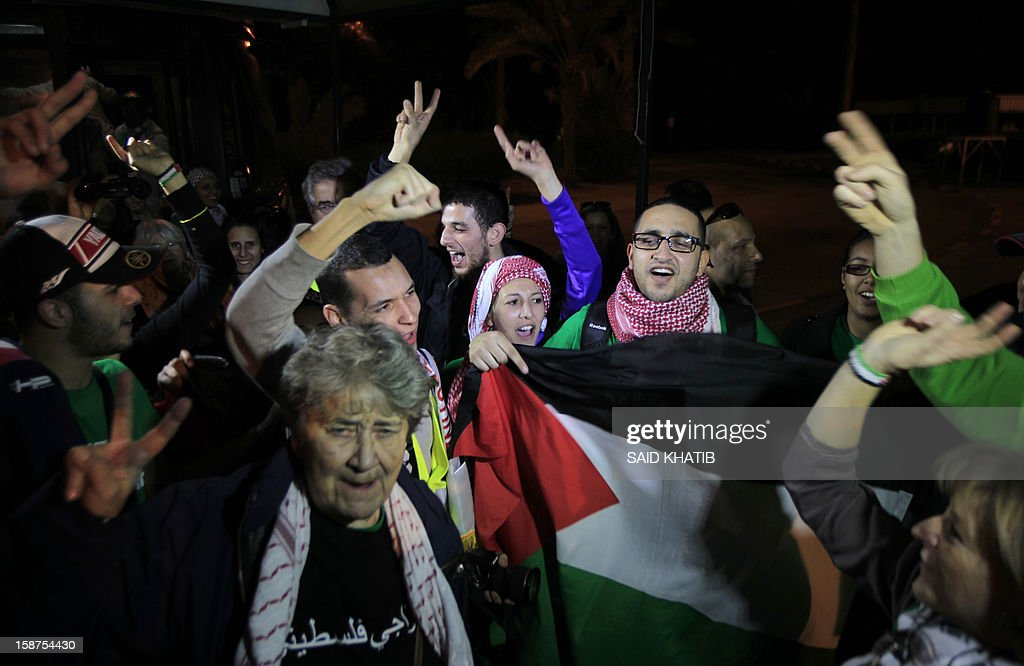 Members of the mostly French and Egyptian delegation of 87 pro-Palestinian activists, flash the sign for victory and wave the Palestinian flag as they arrive in the Gaza Strip via the Rafah border crossing between Egypt and the Palestinian territory on December 27, 2012. Mission 'Welcome to Palestine' aims to denounce the blockade of the Palestinian territory that was imposed in June 2006.