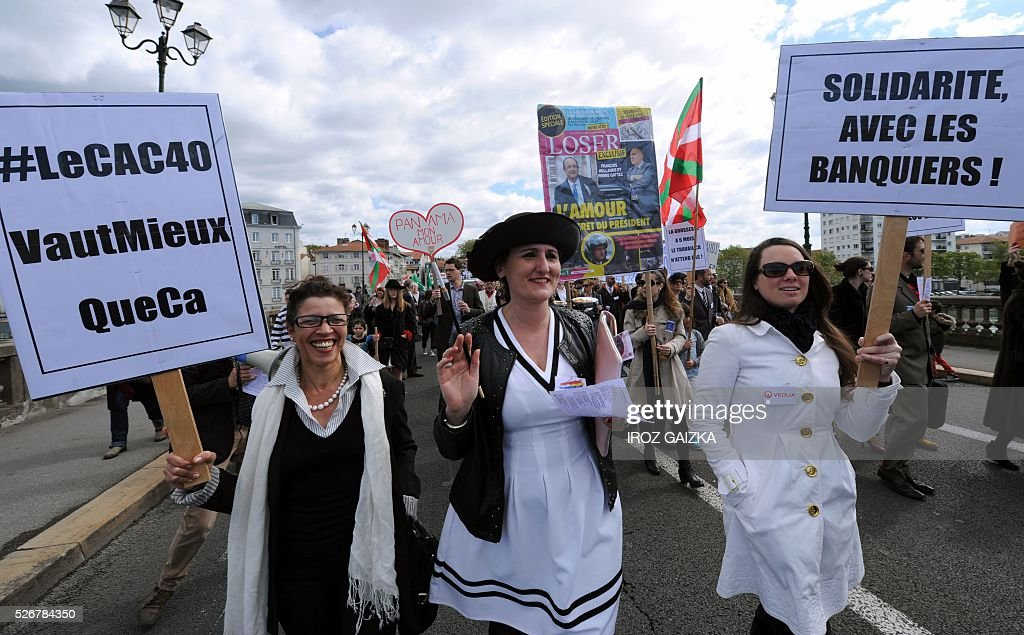 Members of the movement 'Bizi !' ('live' in Basque) hold signs reading 'Solidarity with bankers' (R) and '#TheCAC40IsWorthMoreThanThis' as they stage a 'Rich peoples protest' to mark May Day in Bayonne on May 1, 2016. / AFP / IROZ