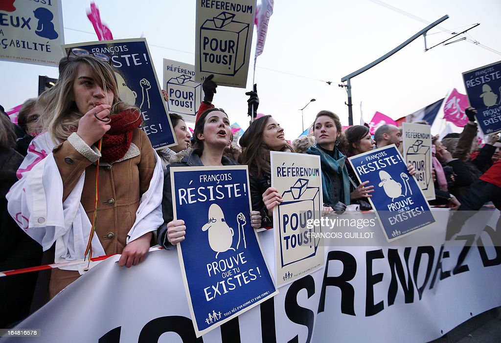 Members of the movement 'La Manif Pour Tous', who are opposed to same-sex marriage, hold placards and chant during a protest on March 28, 2013 outside the headquarters of France Television group in Paris, while the French president is interviewed during the broadcast news on the TV channel France 2. Placards read 'Francois, resist, prove that you exist!' and 'Referendum for all!'.