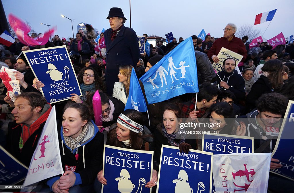 Members of the movement 'La Manif Pour Tous', who are opposed to same-sex marriage, hold placards and chant during a protest on March 28, 2013 outside the headquarters of France Television group in Paris, while the French president is interviewed during the broadcast news on the TV channel France 2. Placards read 'Francois, resist, prove that you exist!'.