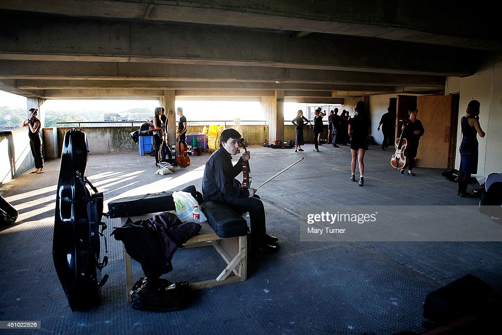 Members of the MultiStory Orchestra prepare before a performance of Jean Sibelius' 5th Symphony in Peckham Rye car park on June 21 2014 in London...