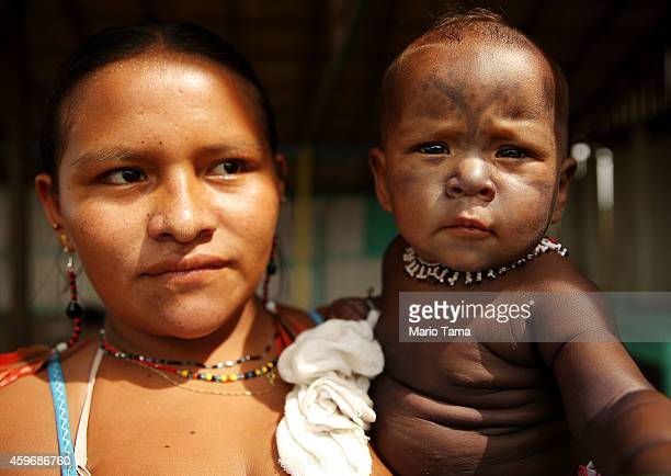 A members of the Munduruku indigenous tribe holds a young child wearing traditional face paint during a 'Caravan of Resistance'' protest by...