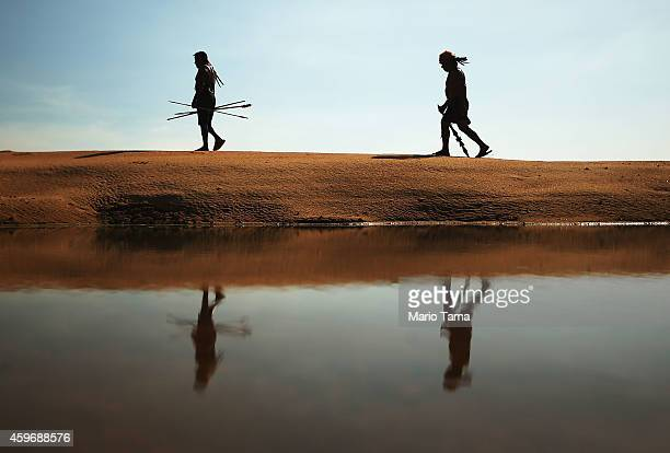Members of the Munduruku indigenous tribe walk along the banks of the Tapajos River as they prepare to protest against plans to construct a...