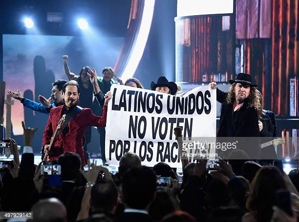 Members of the music groups Mana and Los Tigres Del Norte hold up a sign onstage during the 16th Latin GRAMMY Awards at the MGM Grand Garden Arena on...
