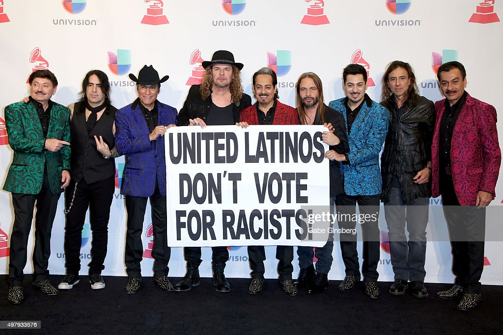 Members of the music groups Mana and Los Tigres Del Norte hold up a sign as they pose in the press room during the 16th Latin GRAMMY Awards at the MGM Grand Garden Arena on November 19, 2015 in Las Vegas, Nevada.
