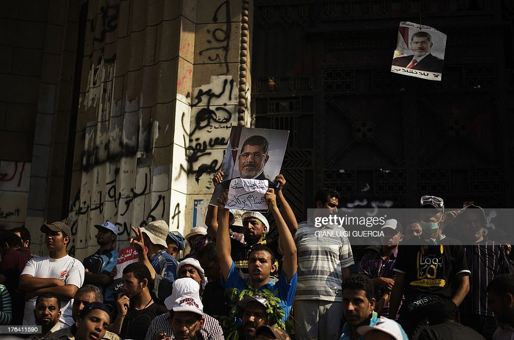 Members of the Muslim Brotherhood and supporters of Egypt's ousted president Mohammed Morsi (portrait) demonstrate outside the High Court in Cairo on August 12, 2013. Egypt's judiciary said it was extending Morsi's detention for a further 15 days pending an investigation into his collaboration with Hamas, which rules neighbouring Gaza.