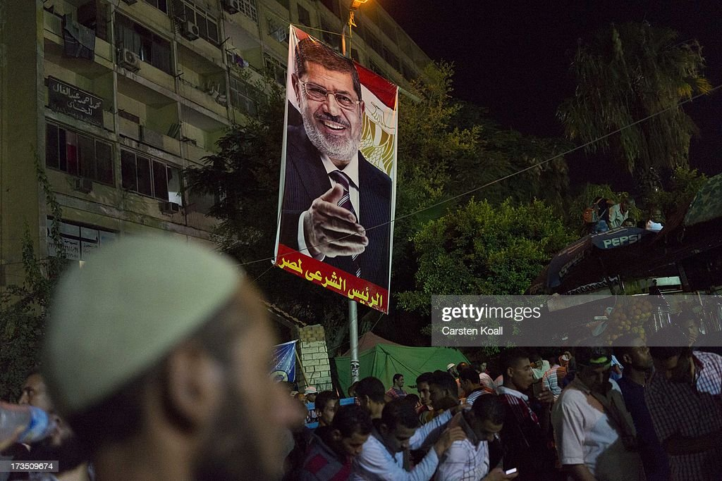 Members of the Muslim Brotherhood and supporters of ousted president Mohamed Morsi hold a poster where is pictured Mohamed Morsi at a rally outside Rabaa al-Adawiya mosque on July 15, 2013 in Cairo, Egypt. Senior US official William Burns has arrived in Egypt for the first time since the overthrow of Mohamed Morsi.