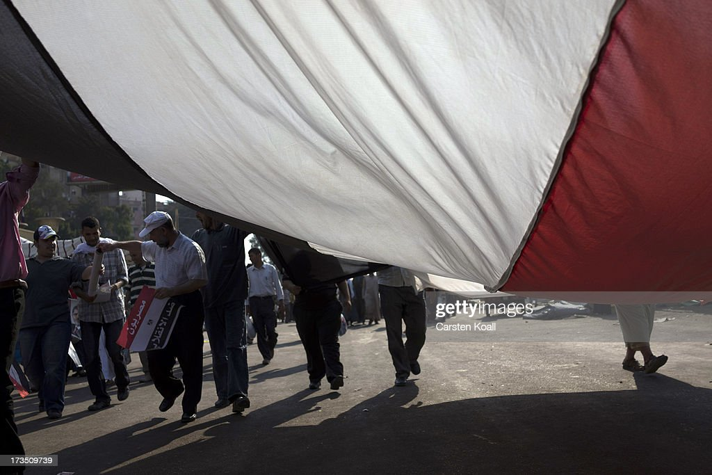 Members of the Muslim Brotherhood and supporters of ousted president Mohamed Morsi shout slogans and wave national flags at a rally outside Rabaa al-Adawiya mosque on July 15, 2013 in Cairo, Egypt. Senior US official William Burns has arrived in Egypt for the first time since the overthrow of Mohamed Morsi.