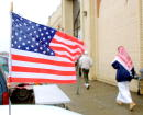 Members of the Muslim community enter a mosque while a tattered American flag flys from the antenna of a parked car November 30 2001 in Dearborn MI...