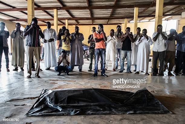 Members of the Muslim community from the flashpoint Muslim PK5 neighbourhood of the capital Bangui mourn over the body of Zacharia Adam killed by...
