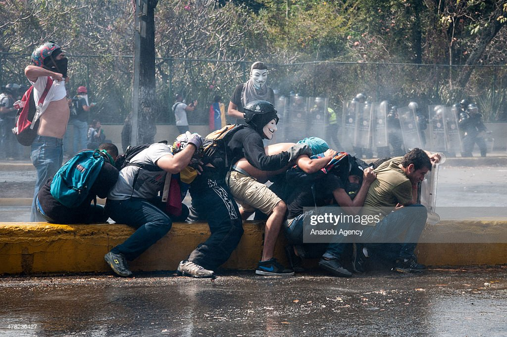 Members of the National Bolivarian Guard use water cannon to disperse protesters during the anti-government protests in Caracas, Venezuela on March 12, 2014. Three people including a university student and a National Guard member, were shot death and several others injured on Wednesday during the anti-government protests in Venezuela.