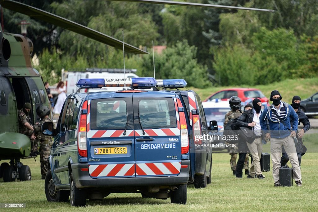 Members of the National Gendarmerie Intervention Group (GIGN) arrive on a sport pitch near the Ensisheim prison, northeastern France, as a psychologist is taken hostage by a prisoner on June 30, 2016. / AFP / SEBASTIEN