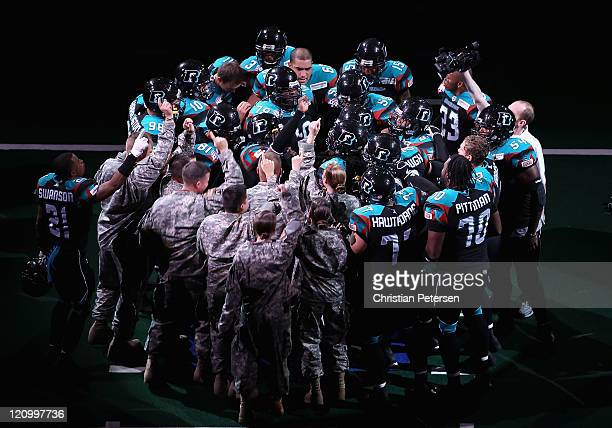 Members of the National Guard and the Arizona Rattlers huddle up before the ArenaBowl XXIV against the Jacksonville Sharks at US Airways Center on...