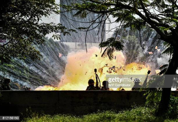 TOPSHOT Members of the National Guard are caught up in a blast during protests in Caracas on July 10 2017 Venezuela hit its 100th day of...
