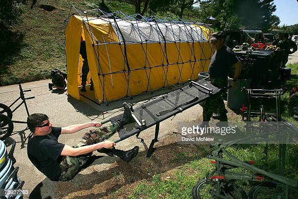 Members of the National Guard set up stretchers during an exercise simulating mass casualties from the collision between a singleengine Cessna and a...
