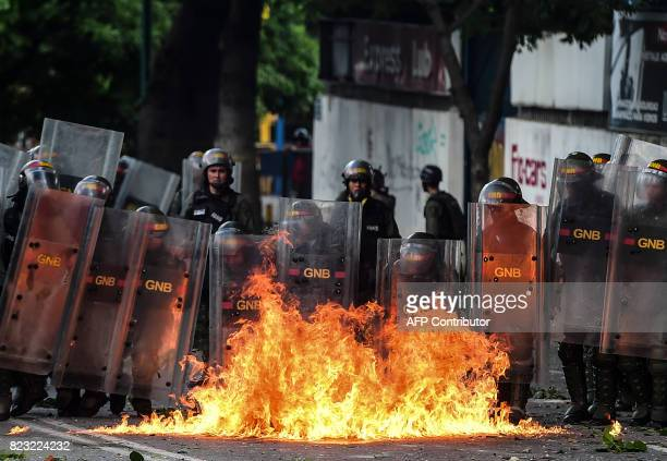 Members of the National Guard use their shields behind a fire during clashes with antigovernment demonstrators in Caracas on July 26 2017 Venezuelans...