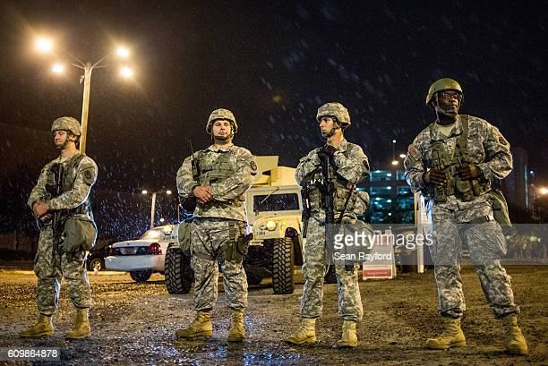 Members of the National Guard watch as demonstrators march in the rain on September 22 2016 in Charlotte NC Protests began on Tuesday night following...