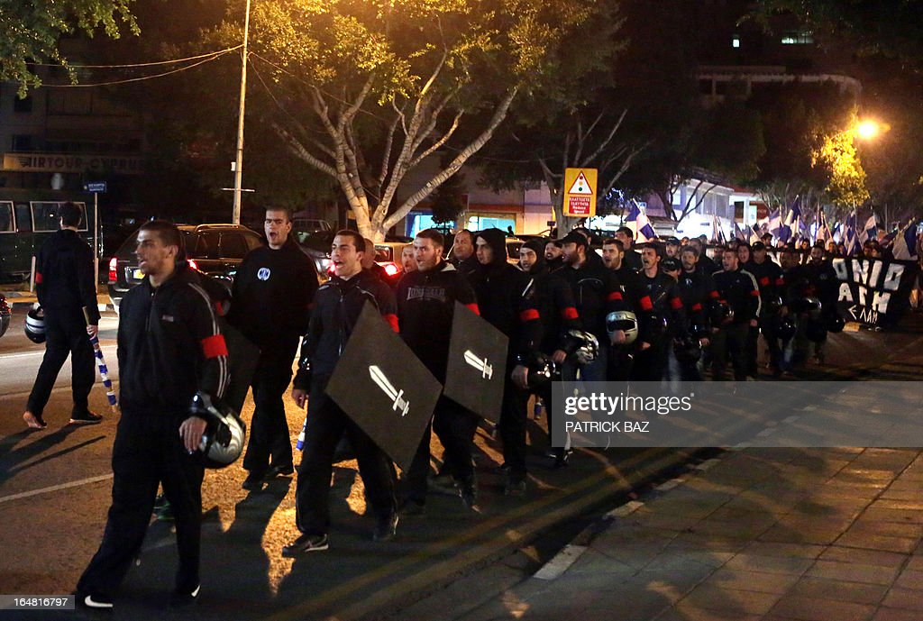 Members of the nationalist Cypriot party Elam (National Popular Front) hold shields and helmets as they march in the center of Nicosia to protest against the measures imposed on the banking sector on March 28, 2013.