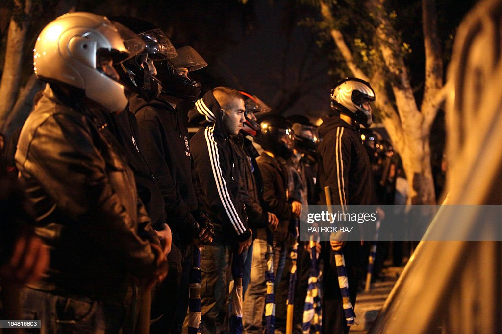 Members of the nationalist Cypriot party Elam (National Popular Front) wearing helmets face riot police during a protest against the measures imposed on the banking sector on March 28, 2013 outside the parliament in Nicosia.