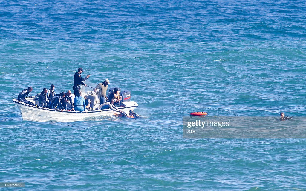 Members of the Navy find the corpse of one of the two victims of a plane that cashed and fell into the sea during the Caribbean Air Show in Santo Domingo on April 7, 2013. Pilot Rafael Sanchez Astacio and Carlos Manuel Guerrero Guerrero died when their plane crashed into the sea some 15 minuts after the start of the show. AFP PHOTO/Erika SANTELICES