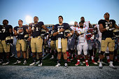 Members of the Navy Midshipmen and Rutgers Scarlet Knights stand together following Rutgers 3124 win at Navy Marine Corps Memorial Stadium on...