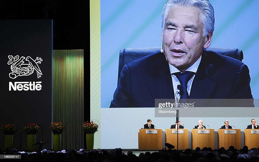 Members of the Nestle SA board listen as a giant screen displays an image of Peter Brabeck-Letmathe, chairman of Nestle SA, during his speech at the company's annual general meeting (AGM) in Lausanne, Switzerland, on Thursday, April 11, 2012. Nestle SA's chairman said Switzerland is becoming more difficult as a business location after voters last month approved some of the world's toughest limits on executives' pay. Photographer: Valentin Flauraud/Bloomberg via Getty Images