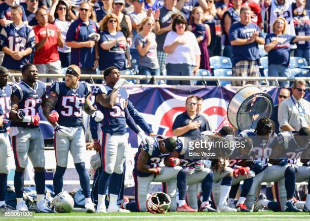 Members of the New England Patriots kneel on the sidelines as the National Anthem is played before a game against the Houston Texans at Gillette...