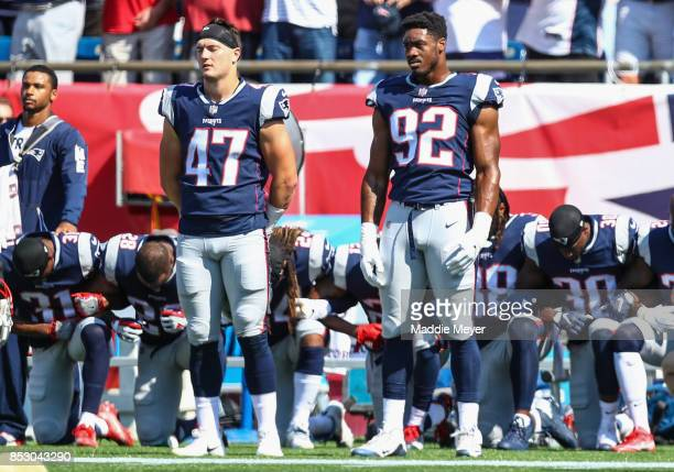 Members of the New England Patriots kneel on the sidelines during the National Anthem before a game against the Houston Texans at Gillette Stadium on...