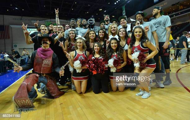 Members of the New Mexico State Aggies cheerleaders dance team and mascot Pistol Pete pose with the trophy following the team's 7060 win over the Cal...