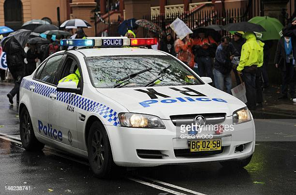 Members of the New South Wales Police Force in a police car help to clear a city street of protesters outside state parliament following a rally by...