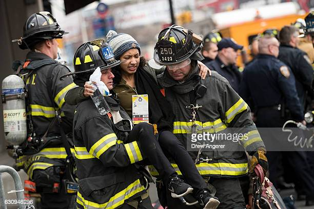 Members of the New York City Fire Department carry an injured person away at the scene of a train derailment at Atlantic Terminal January 4 2017 in...