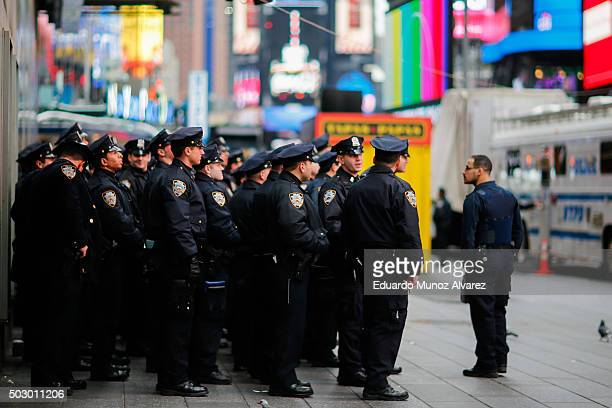 Members of the New York City Police Department wait for instruction at Times Square before New Year's Eve celebrations on December 31 2015 in New...