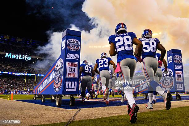 Members of the New York Giants run onto the field before a game against the San Francisco 49ers at MetLife Stadium on October 11 2015 in East...