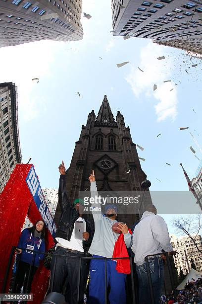 Members of the New York Giants wave to the fans during the New York Giants ticker tape victory parade down the Canyon of Heros on February 7 2012 in...