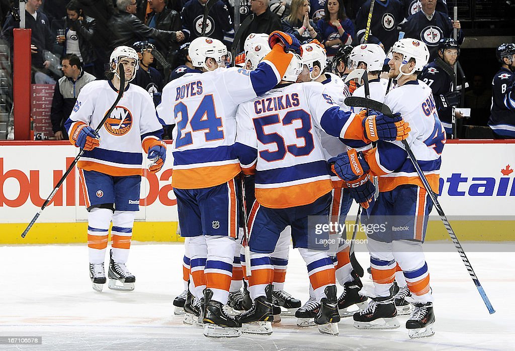 Members of the New York Islanders celebrate on the ice following a 5-4 shootout victory over the Winnipeg Jets at the MTS Centre on April 20, 2013 in Winnipeg, Manitoba, Canada.