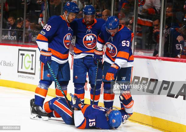 Members of the New York Islanders check on Cal Clutterbuck who crashed into the boards after scoring a third period goal against the Vegas Golden...