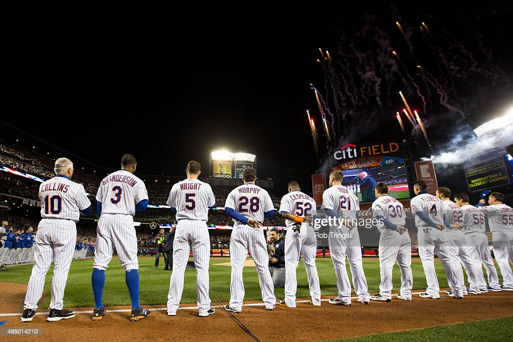 Members of the New York Mets are seen on the base path during the signing of the National Anthem prior to Game 3 of the 2015 World Series against the...