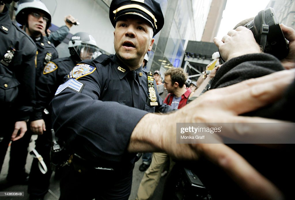 Members of the New York Police Department (NYPD) scuffle with protestors as they guard the entrance to a Citibank as Occupy Wall Street demonstrators march along 42nd Street to protest various businesses during May Day on May 1, 2012 in New York. Demonstrators have called for nation-wide May Day strikes to protest economic inequality and political corruption.