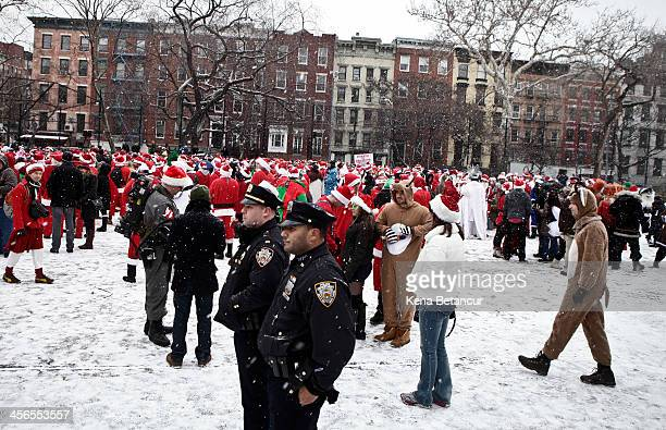 Members of the New York Police Department stand next to revelers dressed as Santa Claus as they gather at Tompkins Square Park during the annual...