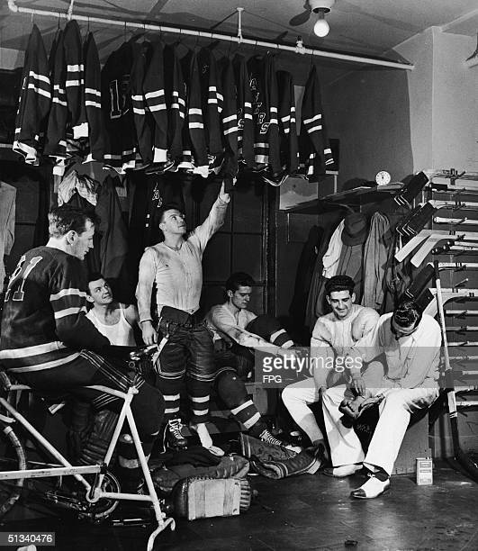 Members of the New York Rangers ice hockey team some in uniform and some in street clothes dress in the locker room in Madison Square Garden New York...