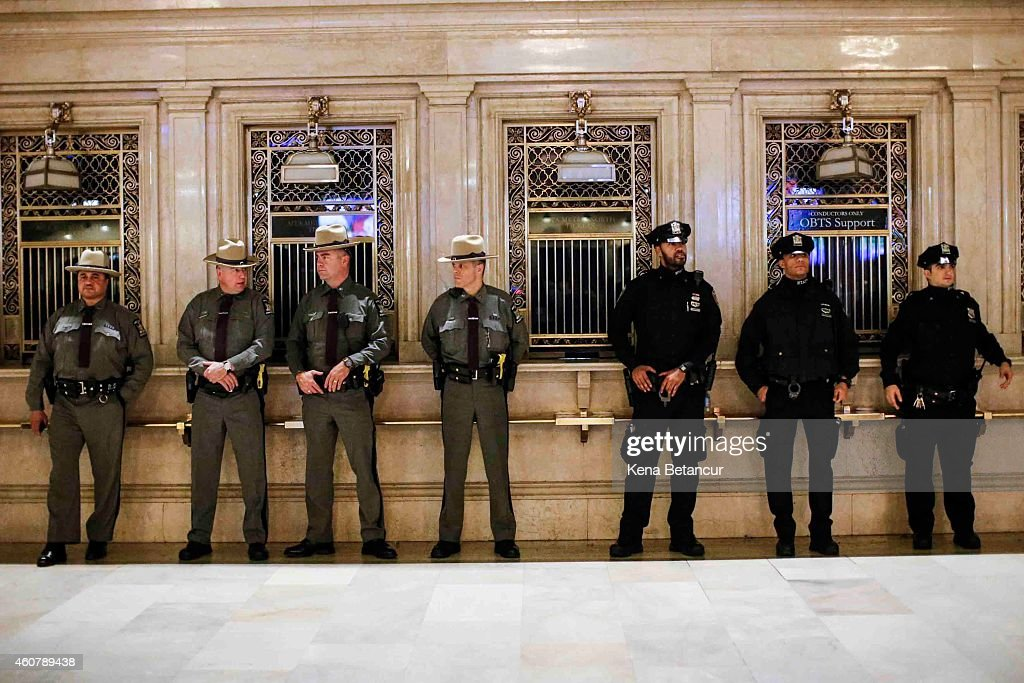 Members of the New York State Police and New York Police Department stand guard while a small group of protestors demonstrate against police...