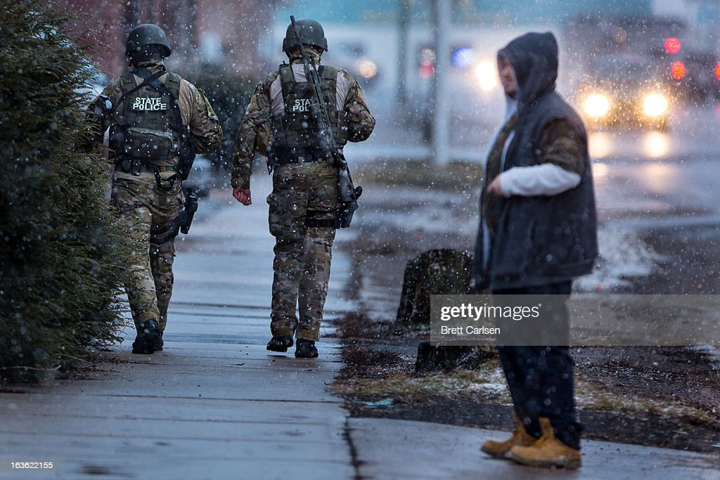 Members of the New York State Police walk past a citizen after switching off with another team for a rooftop position during a standoff with murder suspect Kurt Meyers on March 13, 2013 in Herkimer, New York. Police have identified 64-year-old Kurt Meyers as a possible suspect responsible for a total of four shooting deaths and two injuries across the area earlier in the day.