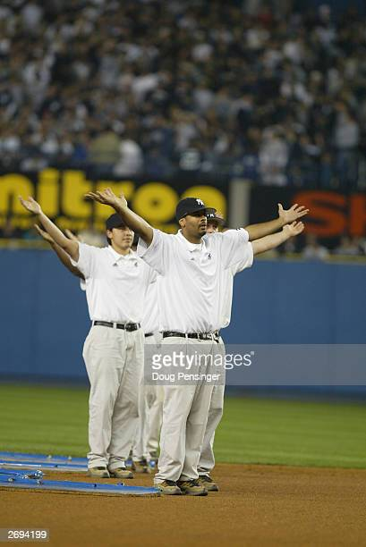 Members of the New York Yankees grounds crew dance to the song 'YMCA' during game 1 of the American League Championship Series against the Boston Red...