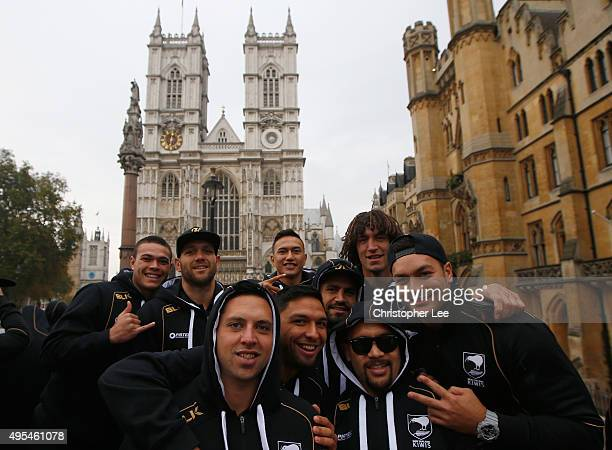 Members of the New Zealand team pose for the camera as they pass Westminster Abbey during an open top bus tour of London on November 3 2015 in London...