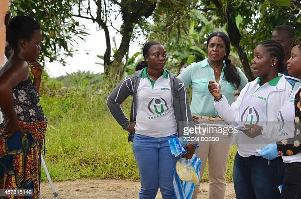 Members of the NGO U Fondation speak with a woman whose quarantined family members are suffering from the Ebola virus on October 16 2014 in Monrovia...