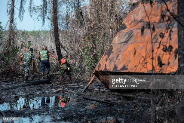 Members of the NNS Delta of the Nigerian Navy forces walk through the oil soaked land at a destroyed illegal oil refinery on April 19 2017 in the...