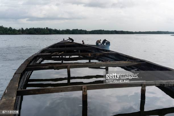 TOPSHOT Members of the NNS Pathfinder of the Nigerian Navy forces come across an abandoned boat filled with oil during a patrol on April 19 2017 in...