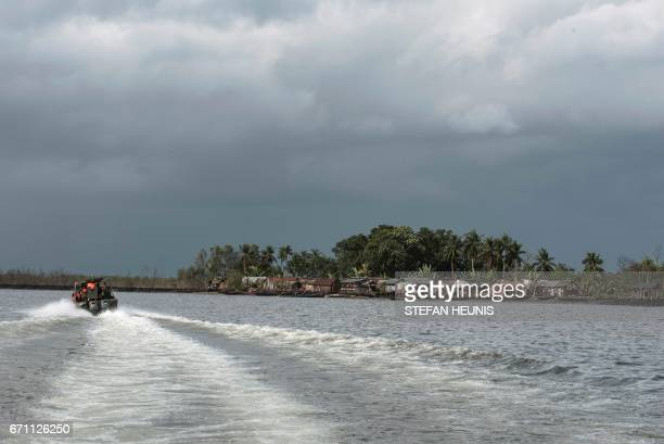 Members of the NNS Pathfinder of the Nigerian Navy forces go on patrol pass a creekside community on April 19 2017 in the Niger Delta region near the...