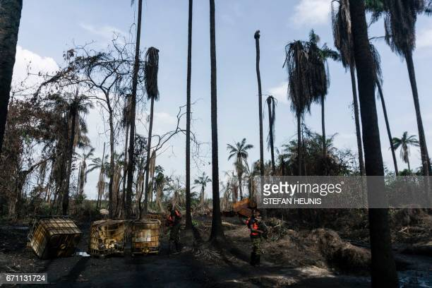 Members of the NNS Pathfinder of the Nigerian Navy forces inspect a destroyed illegal oil refinery on April 19 2017 in the Niger Delta region near...