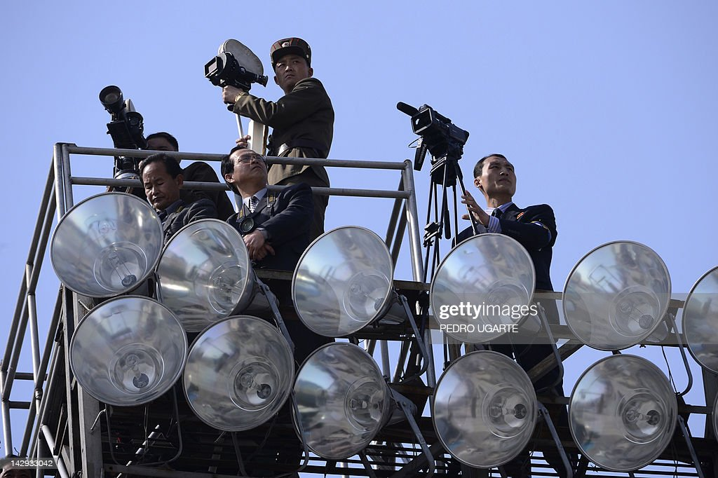 Members of the North Korean media look out from a viewing point during a military parade to mark the 100 birth of the country's founder Kim Il-Sung in Pyongyang on April 15, 2012. to mark 100 years since the birth of North Korea's founder Kim Il-Sung in Pyongyang on April 15, 2012. North Korea's new leader Kim Jong-Un delivered his first public speech on April 15 and vowed to push for 'final victory' for his impoverished state despite a failed rocket launch two days ago.